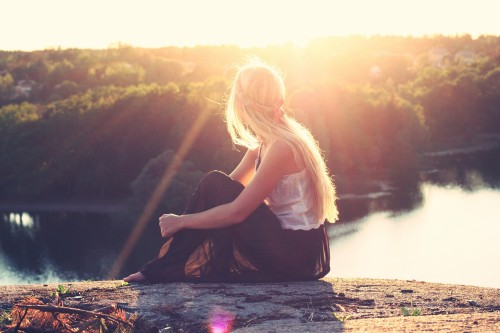young woman in hippie style sitting on riverbank and looking at view